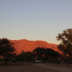 Der angeschlossene Campingplatz fügt sich schon eher in die Landschaft ein und der Sonnenaufgang am Morgen zaubert ein wunderschönes Farbspiel auf den Brandberg im Hintergrund.